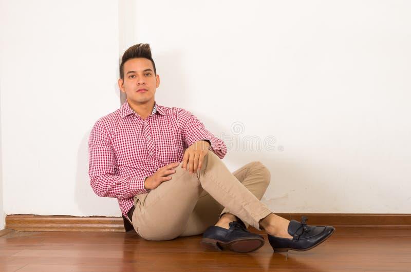 Spaans mannetje die rode witte overhemdszitting dragen royalty-vrije stock afbeelding
