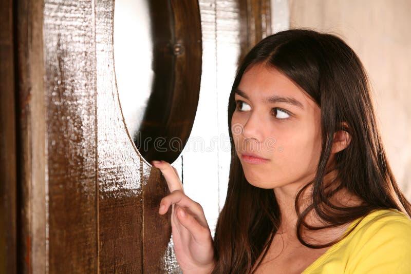 Spaans meisje dat in venster gluurt stock afbeelding