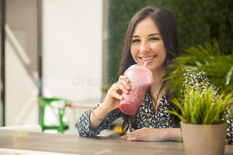 Spaans meisje die een smoothie drinken stock afbeeldingen