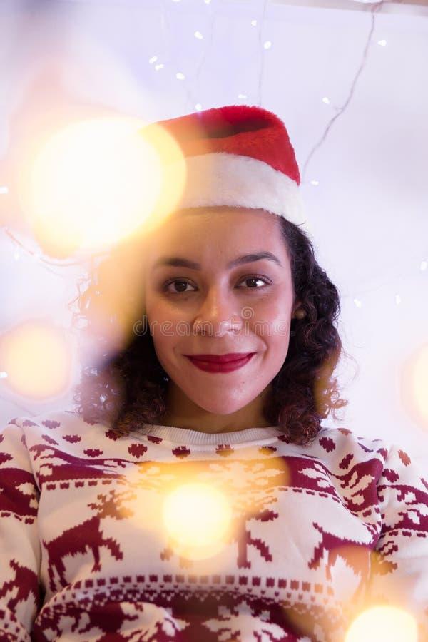 Spaans meisje die Kerstmanhoed en Kerstmissweater thuis dragen decoratie met kleurrijke lichten stock fotografie