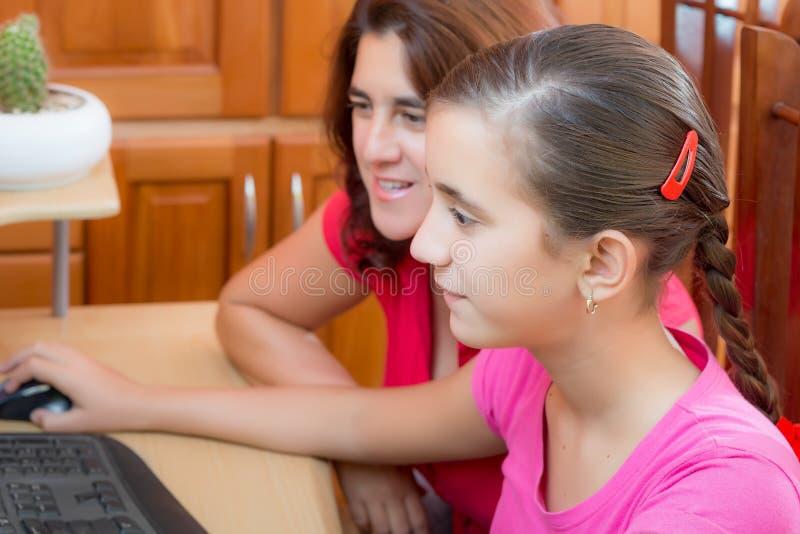 Spaans meisje en haar jonge moeder die aan een computer werken royalty-vrije stock afbeelding