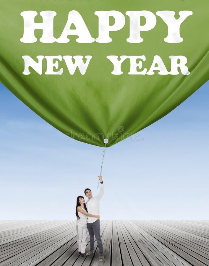 Spaans paar die een banner nieuw jaar trekken stock foto's
