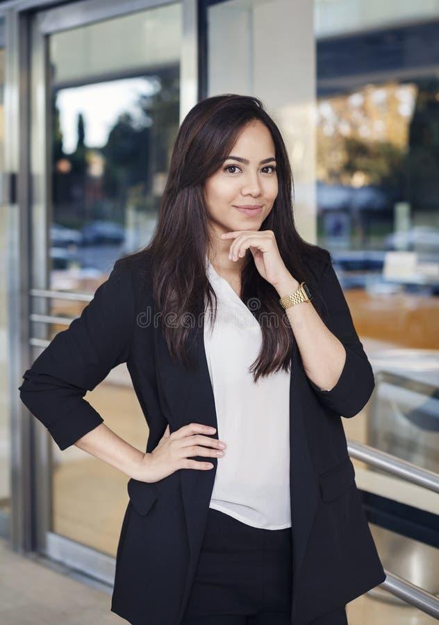 Spaanse bedrijfsvrouw in kostuum lookig bij camera en het glimlachen stock afbeelding