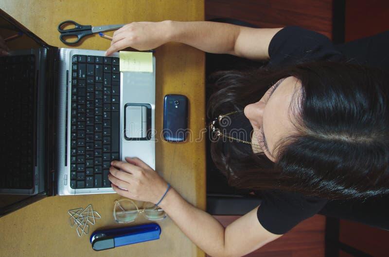 Spaanse donkerbruine bureauvrouw die aan laptop werken royalty-vrije stock afbeeldingen