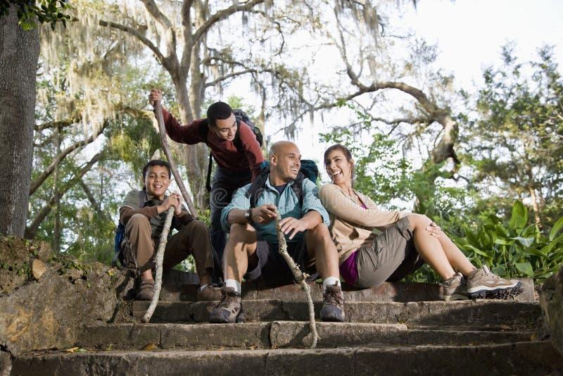 Spaanse familie die met rugzakken in park wandelt stock afbeeldingen