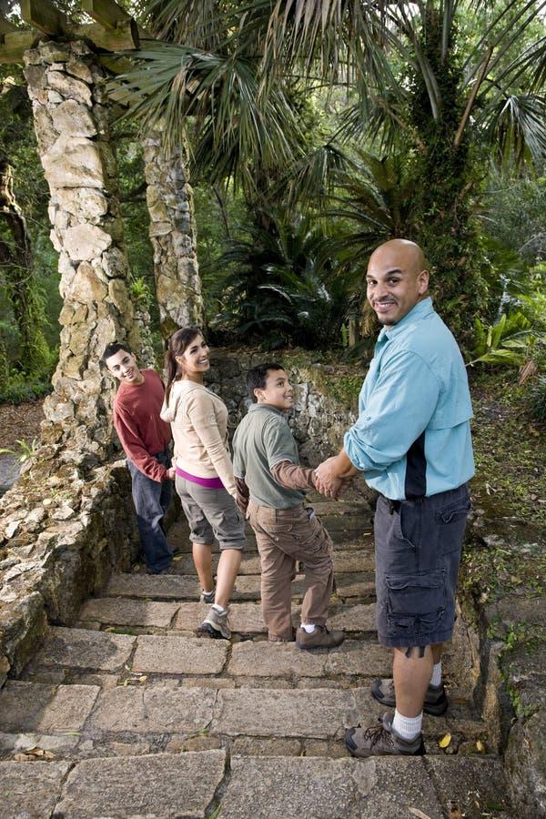 Spaanse familie die onderaan treden in openlucht loopt stock foto