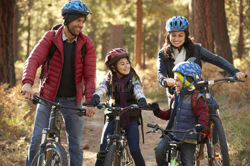 Spaanse familie op fietsen in een bos die elkaar bekijken royalty-vrije stock fotografie