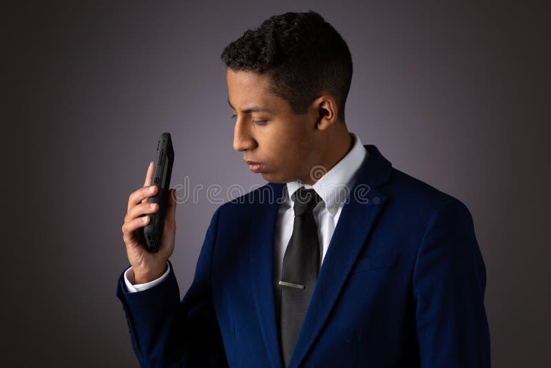 Spaanse Geklede Tiener goed Gekleed in Kostuum, en het Gebruiken van Cellphone, Smartphone stock fotografie