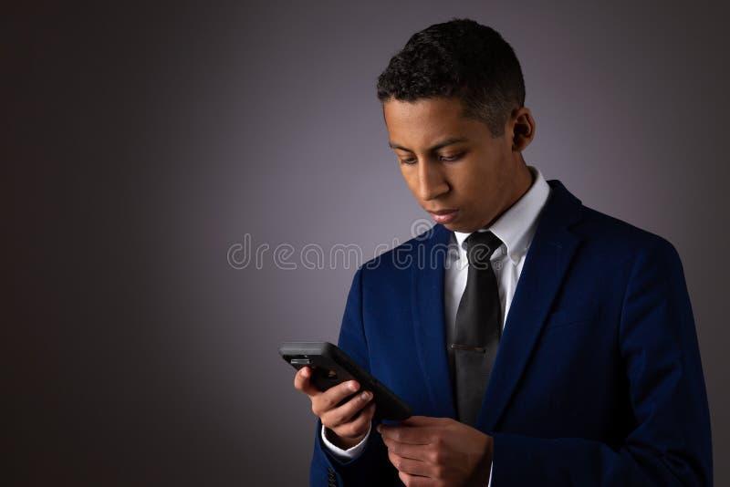 Spaanse Geklede Tiener goed Gekleed in Kostuum, en het Gebruiken van Cellphone, Smartphone royalty-vrije stock afbeelding