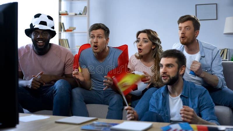 Spaanse groep vrienden het letten op gelijke thuis, ondersteunend nationaal team stock afbeeldingen