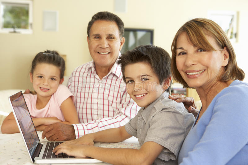 Spaanse Grootouders en Kleinkinderen die Computer thuis met behulp van stock fotografie