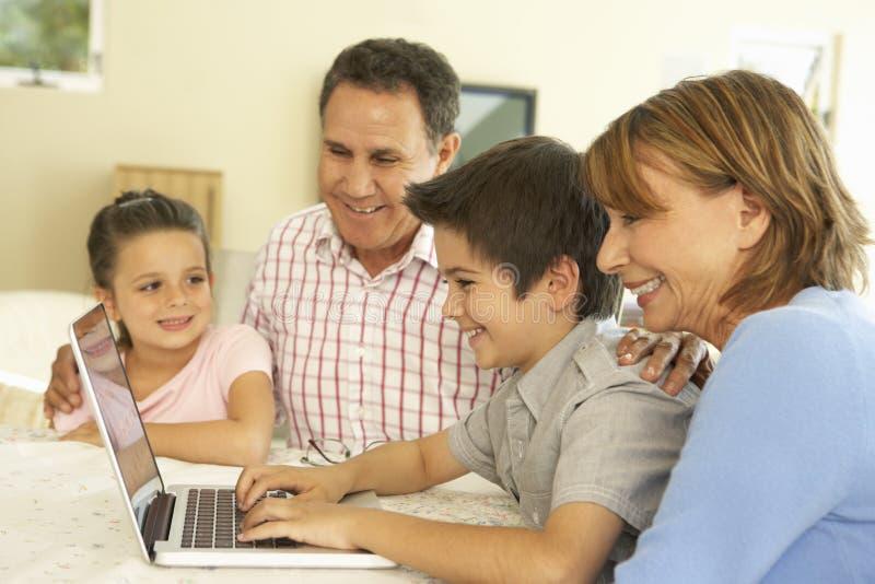 Spaanse Grootouders en Kleinkinderen die Computer thuis met behulp van stock foto