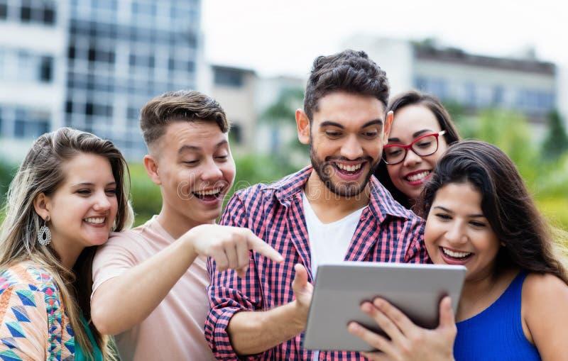 Spaanse hipsterstudent met tabletcomputer en groep het toejuichen van internationale studenten stock foto's