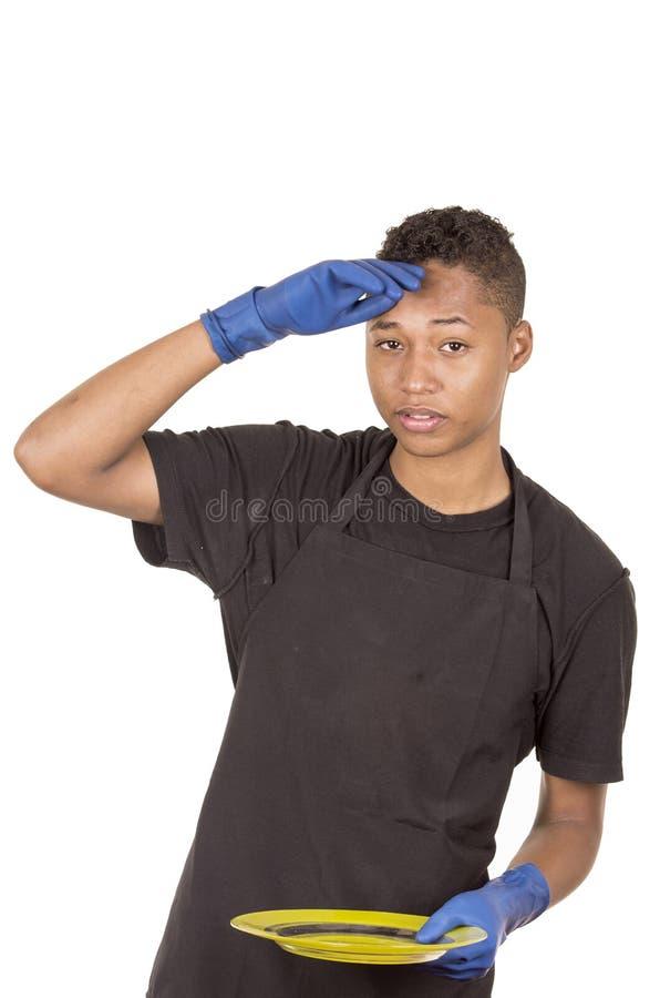 Spaanse jonge mens die blauwe schoonmakende handschoenen dragen stock fotografie