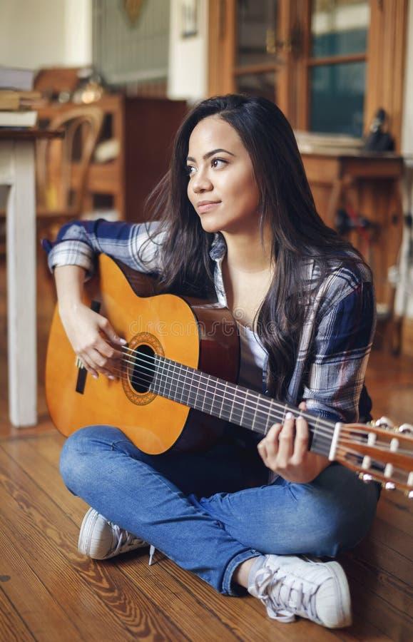 Spaanse jonge vrouw die akoestische gitaar spelen stock foto