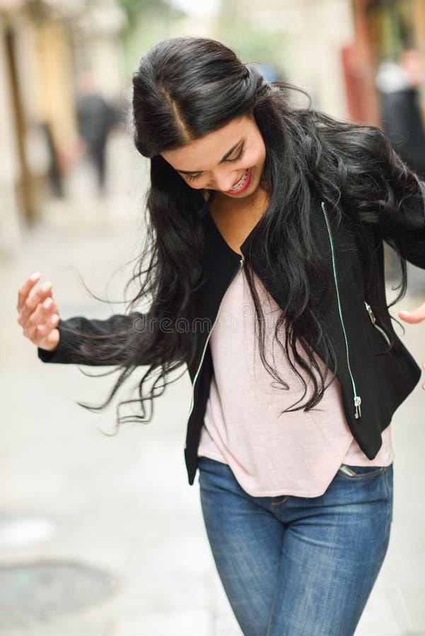 Spaanse jonge vrouw die vrijetijdskleding op stedelijke achtergrond dragen stock foto's