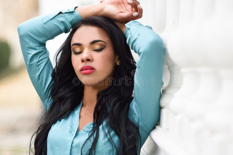 Spaanse jonge vrouw die vrijetijdskleding op stedelijke achtergrond dragen royalty-vrije stock foto