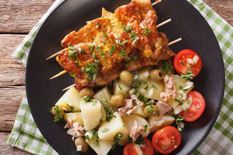 Spaanse kebab Pinchos Morunos en dicht-u van saladepatatas Alinadas royalty-vrije stock foto