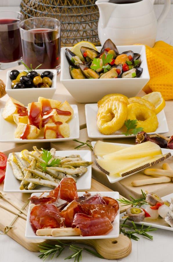 Spaanse Keuken. Verscheidenheid van tapas op witte platen. royalty-vrije stock afbeelding