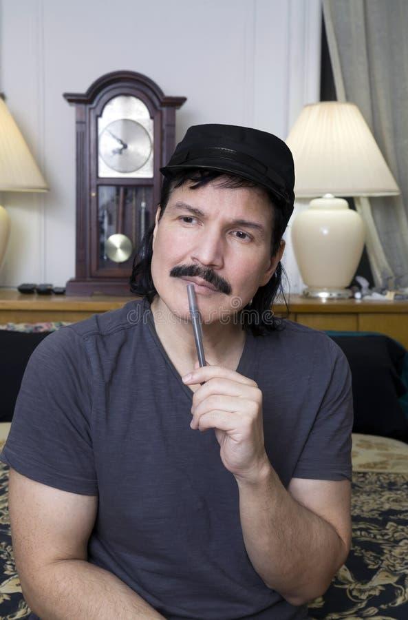 Spaanse mens die met pen in slaapkamer aangezien hij sists op bed denken stock foto's
