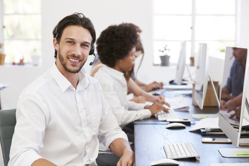 Spaanse mens met hoofdtelefoon bij het glimlachen aan camera in een bureau stock fotografie