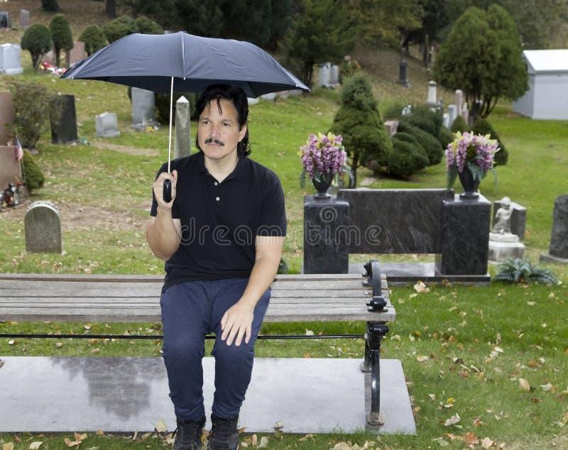 Spaanse mensenzitting met paraplu in begraafplaats stock fotografie