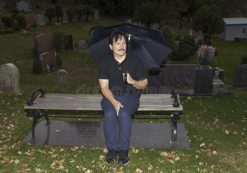 Spaanse mensenzitting met paraplu in begraafplaats royalty-vrije stock foto