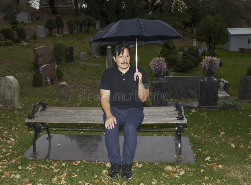 Spaanse mensenzitting met paraplu in begraafplaats stock foto