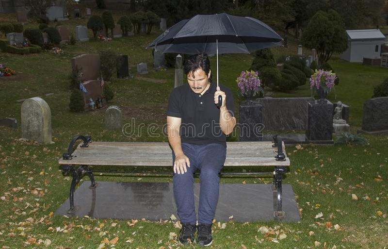 Spaanse mensenzitting op bank met verminderd hoofd in begraafplaats stock afbeeldingen