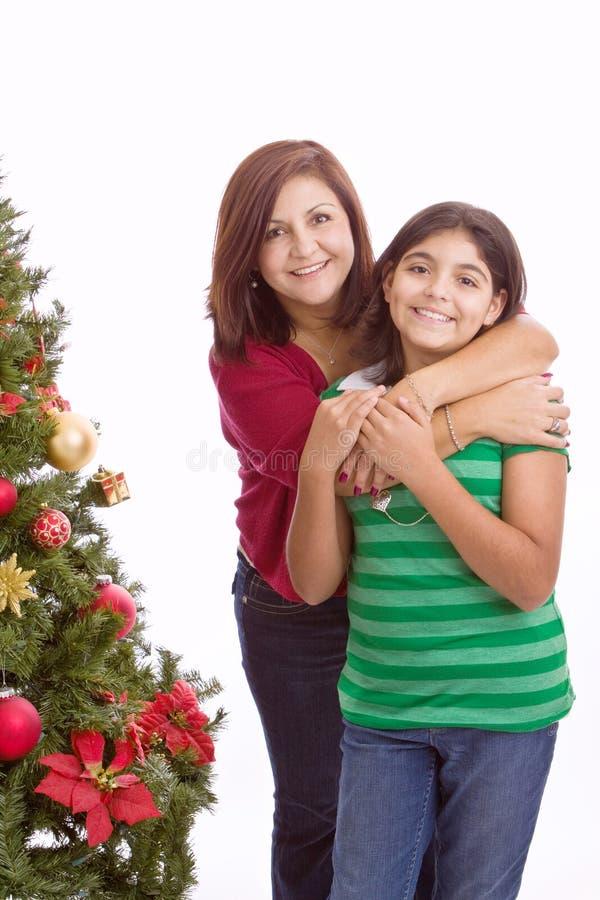 Spaanse moeder die haar dochter koesteren bij Kerstmis royalty-vrije stock foto