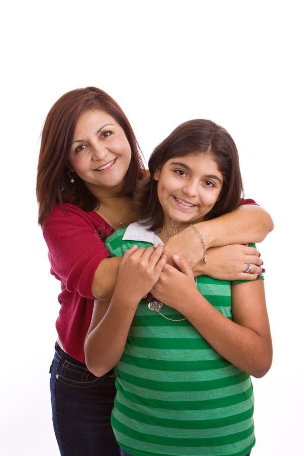Spaanse moeder die haar die dochter koesteren op wit wordt geïsoleerd stock afbeelding