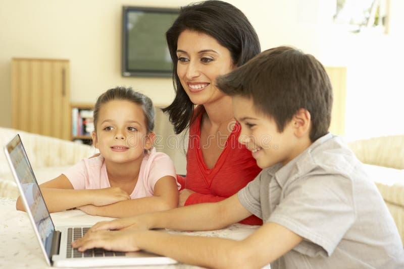 Spaanse Moeder en Kinderen die Computer thuis met behulp van royalty-vrije stock fotografie