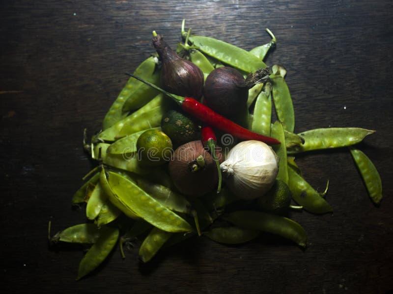 Spaanse peper, ui, knoflook, en bonen op een houten achtergrond stock afbeeldingen