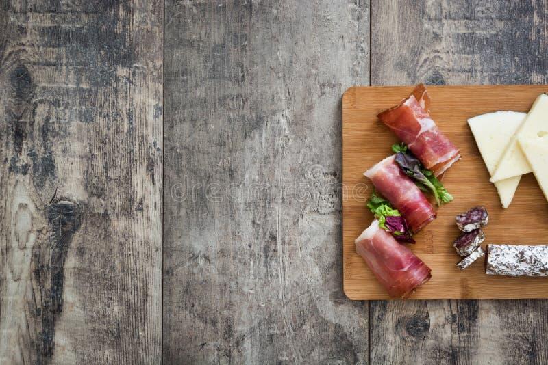 Spaanse serranoham, kaas en worst op een rustieke houten achtergrond stock afbeelding