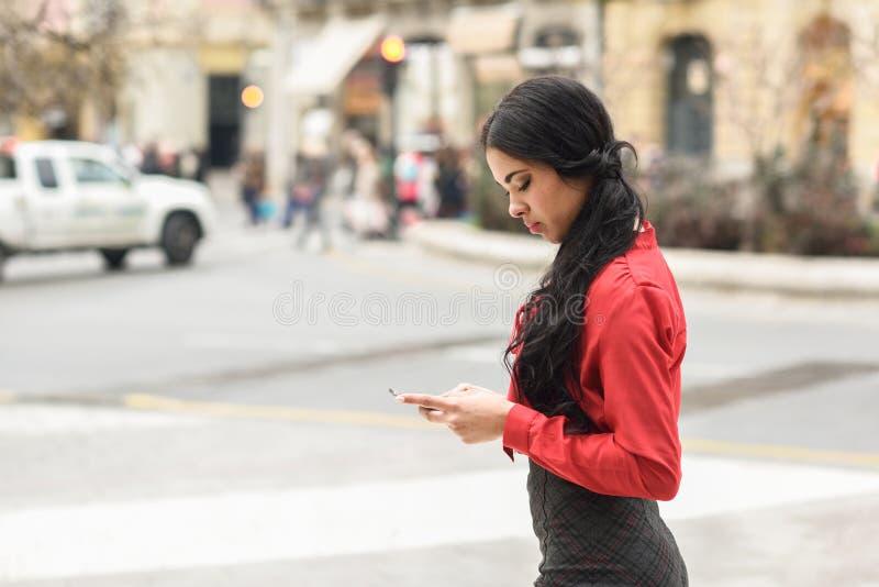 Spaanse stewardess die op stedelijke achtergrond haar mobiele ph bekijken stock afbeeldingen