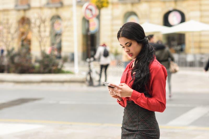 Spaanse stewardess die op stedelijke achtergrond haar mobiele ph bekijken royalty-vrije stock fotografie