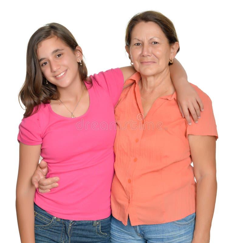 Spaanse tiener en haar die grootmoeder op wit wordt geïsoleerd royalty-vrije stock foto's