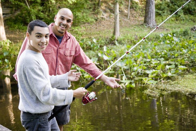 Spaanse tiener en vader die in vijver vissen stock foto