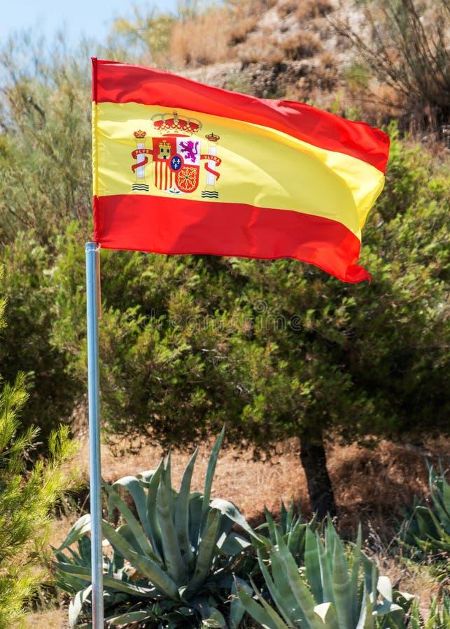 Spaanse vlag tegen authentiek Spaans platteland royalty-vrije stock afbeelding