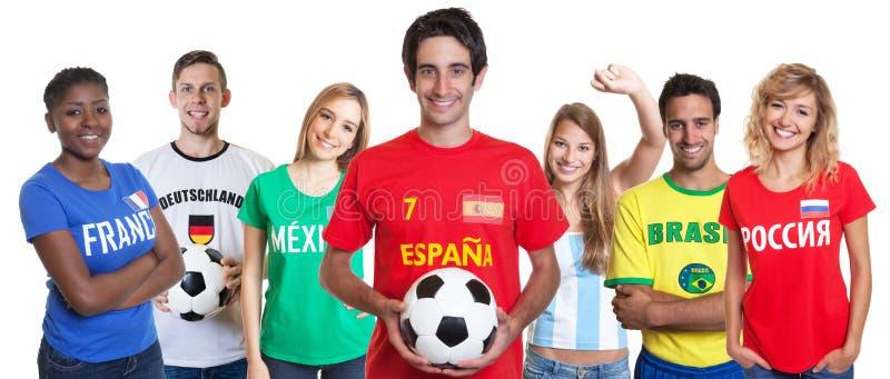 Spaanse voetbalventilator met bal en het toejuichen van groep andere ventilators stock afbeelding