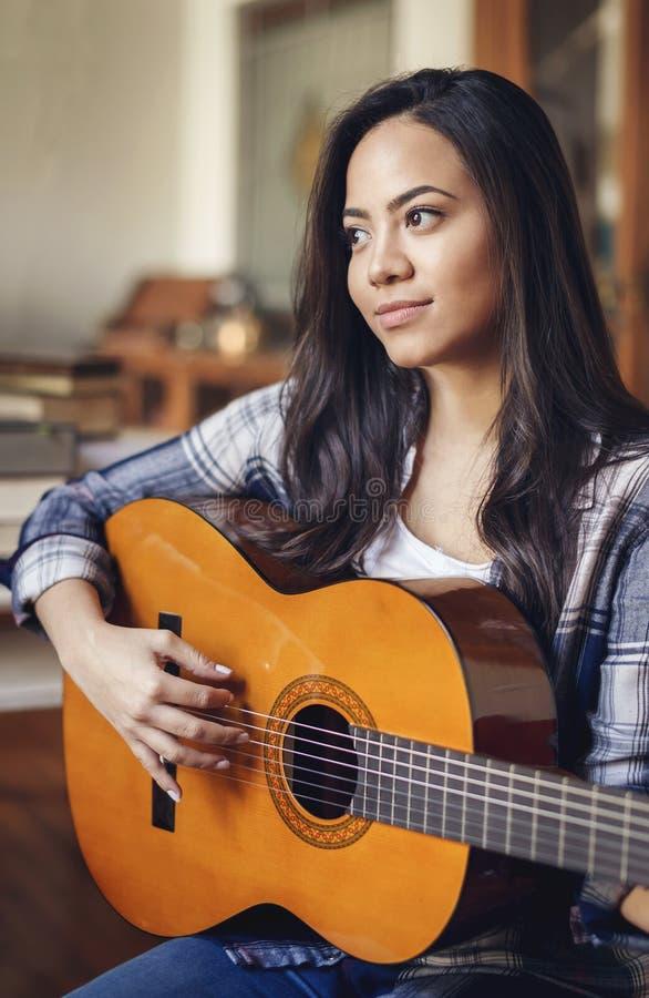 Spaanse vrouw die akoestische gitaar spelen royalty-vrije stock afbeeldingen