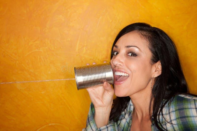 Spaanse vrouw met de telefoon van het tinblik stock fotografie
