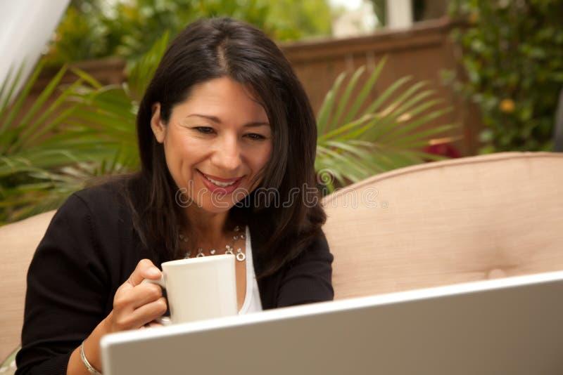 Spaanse Vrouw met Koffie en Laptop stock afbeelding