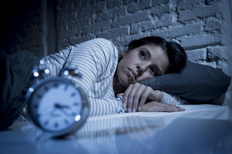 Spaanse vrouwen thuis slaapkamer die in bed laat bij nacht liggen die aan slaap proberen die aan slapeloosheid lijden stock fotografie