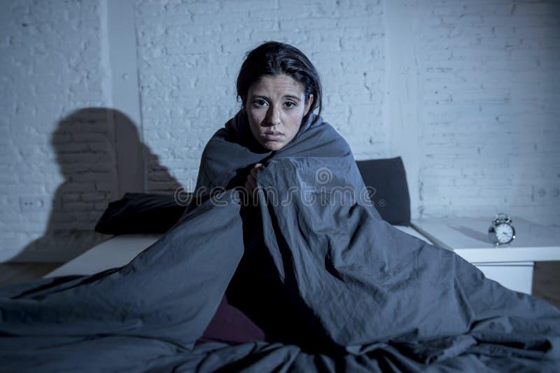 Spaanse vrouwen thuis slaapkamer die in bed laat bij nacht liggen die aan slaap proberen die aan slapeloosheid lijden royalty-vrije stock fotografie