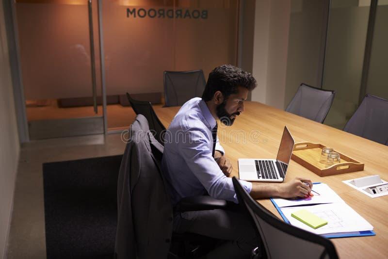 Spaanse zakenman die laat in bureau, opgeheven mening werken royalty-vrije stock afbeelding