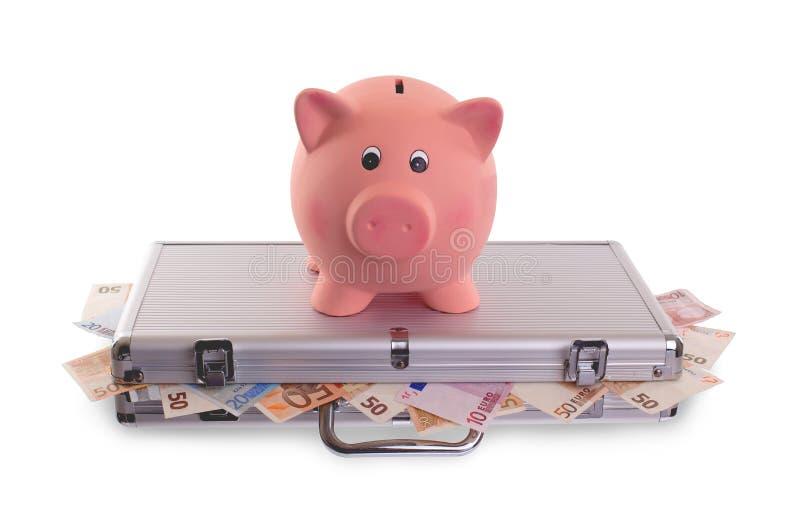 Spaarvarken bovenop metaalgeval met geld wordt gevuld dat stock afbeeldingen