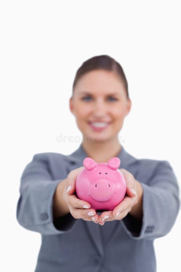 Spaarvarken dat door glimlachende bankbediende wordt aangeboden stock afbeelding