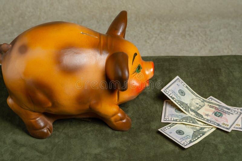 Spaarvarken en dollars op een groene achtergrond royalty-vrije stock foto's