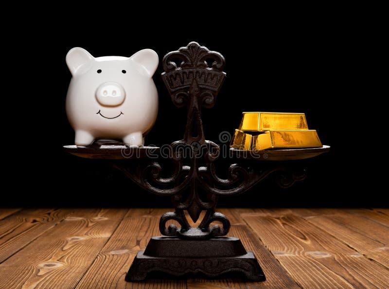 Spaarvarken en goudstaven op evenwichtige schaal royalty-vrije stock afbeeldingen